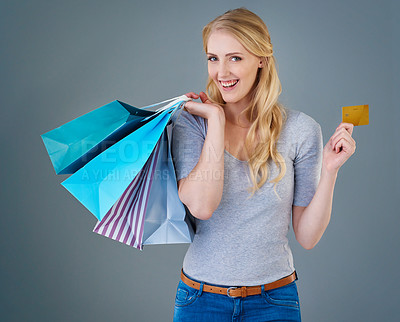 Buy stock photo Cropped studio shot of a young woman holding up shopping bags and her credit card