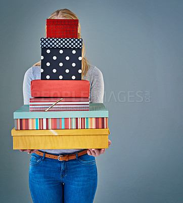 Buy stock photo Cropped studio shot of a young woman holding a stack of presents in front of her face