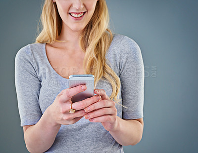 Buy stock photo Cropped studio shot of a young woman looking at her smartphone