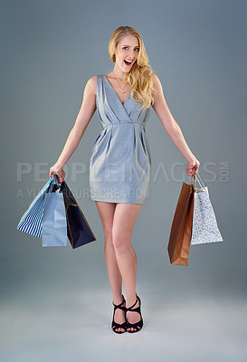 Buy stock photo Full length studio shot of a happy young woman holding a selection of shopping bags