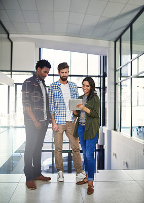 Buy stock photo Shot of three young designers working on a digital tablet in a modern office