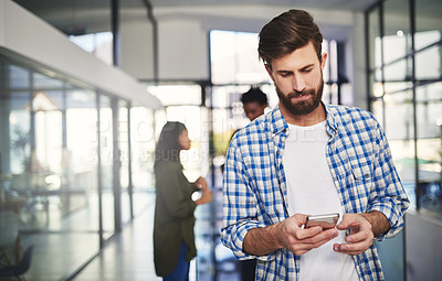 Buy stock photo Cropped shot of a young designer using a cellphone in an office with colleagues in the background