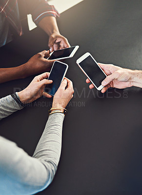 Buy stock photo Cropped shot of three people  sitting around a table together and using their cellphones