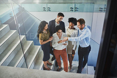 Buy stock photo High angle shot of a group of coworkers looking at a tablet while standing on a staircase in the office