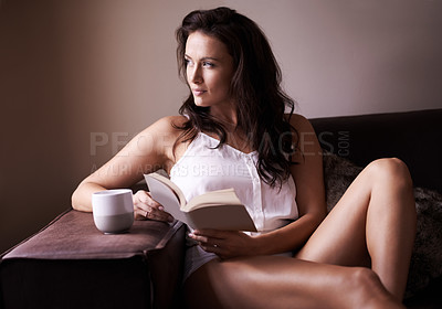 Buy stock photo Shot of a beautiful woman relaxing with a book at home