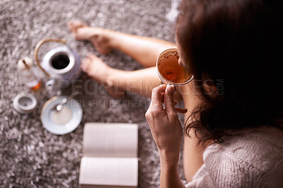 Buy stock photo Cropped shot of a woman having tea while reading a book