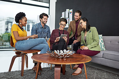 Buy stock photo Shot of a group of creative businesspeople looking at something on a tablet