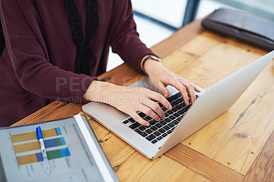 Buy stock photo Cropped shot of an unidentifiable woman using her laptop in the office