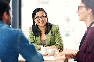 Buy stock photo Portrait of a young businesswoman sitting in a meeting with her colleagues