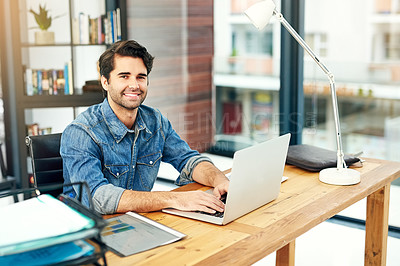Buy stock photo Portrait of a young designer working on a laptop in a modern office