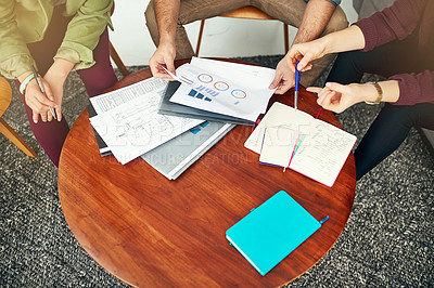 Buy stock photo High angle shot of people looking through some paperwork in an office