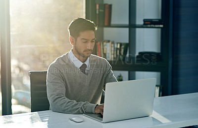 Buy stock photo Cropped shot of a young businessman working on his laptop