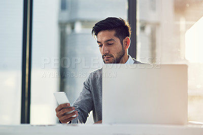Buy stock photo Cropped shot of a young businessman using his cellphone in the office