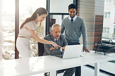 Buy stock photo Cropped shot of three businesspeople working on a laptop in their office