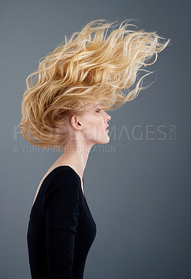 Buy stock photo Studio shot of an attractive young woman tossing her beautiful long blonde hair against a gray background