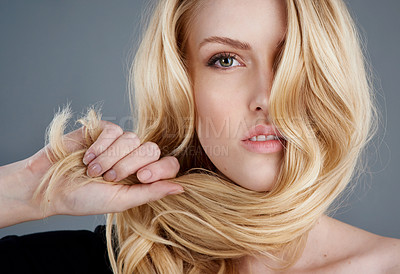 Buy stock photo Studio portrait of an attractive young woman tugging her blonde hair against a gray background