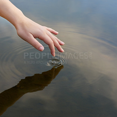Buy stock photo Cropped shot of a finger touching water to form ripples