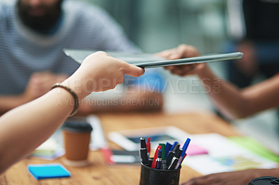 Buy stock photo Cropped shot of an unidentifiable businessperson passing a file to a colleague