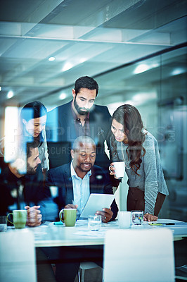 Buy stock photo Shot of a group of businesspeople coming together to discuss something on a digital tablet