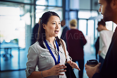 Buy stock photo Shot of two businesspeople having a discussion with colleagues blurred in the background