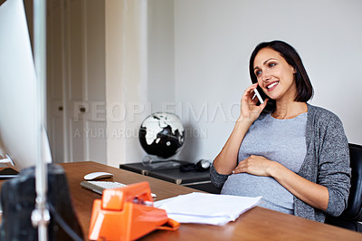 Buy stock photo Shot of a pregnant women using her phone while working in her home office