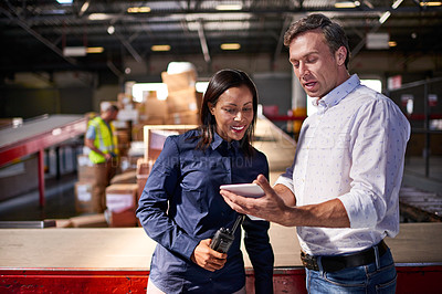 Buy stock photo Shot of two colleagues looking at a digital tablet while standing in a large warehouse