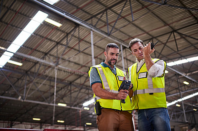 Buy stock photo Low angle shot of two warehouse workers standing in a large warehouse