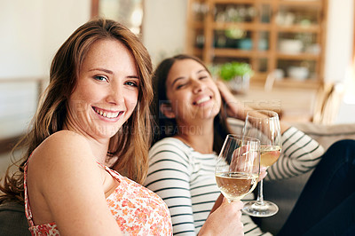 Buy stock photo Portrait of two young friends drinking wine while relaxing on the sofa