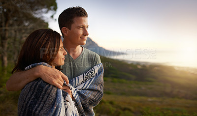 Buy stock photo Shot of a young couple wrapped together in a blanket outdoors