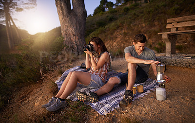 Buy stock photo Shot of a young woman taking pictures with her camera while her boyfriend prepares a pot of coffee on their date outdoors