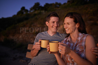 Buy stock photo Shot of a happy young couple enjoying a beverage together on an evening date outdoors