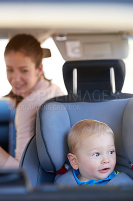 Buy stock photo Cropped shot of a mother sitting in a car with her baby boy in a car seat