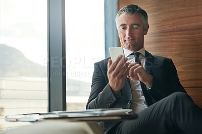 Buy stock photo Shot of a mature businessman using his phone at work