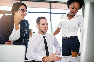 Buy stock photo Cropped shot of a group of businesspeople gathered around a computer in their office
