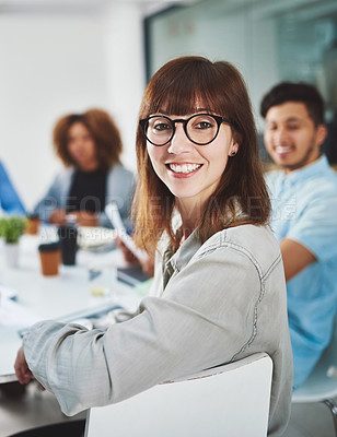 Buy stock photo Cropped portrait of a young businesswoman looking over her shoulder while sitting in a boardroom with her colleagues