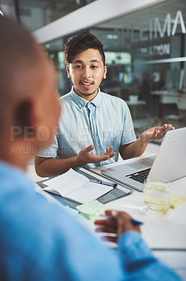 Buy stock photo Cropped shot of a young businessman explaining something to his colleague in the boardroom