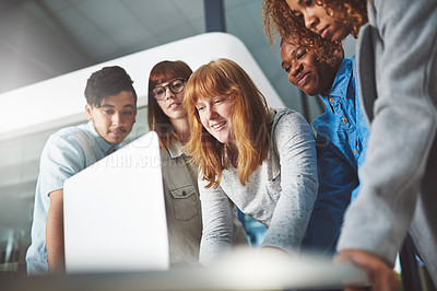 Buy stock photo Cropped shot of a group of young businesspeople huddled around a laptop in their office