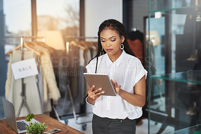 Buy stock photo Cropped shot of a young business owner using her tablet while standing in her store