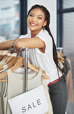 Buy stock photo Cropped portrait of young woman leaning on a clothing rail with a sign that reads