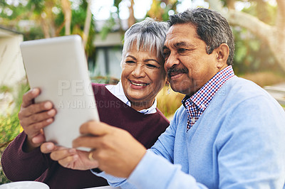 Buy stock photo Shot of an older couple using a digital tablet together outdoors