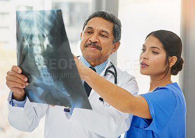 Buy stock photo Shot of a mature doctor and young nurse looking at an x ray together