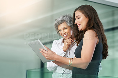 Buy stock photo Cropped shot of colleagues working together on a digital tablet in a modern office