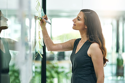 Buy stock photo Cropped shot of a young businesswoman writing notes on a glass wall in a modern office