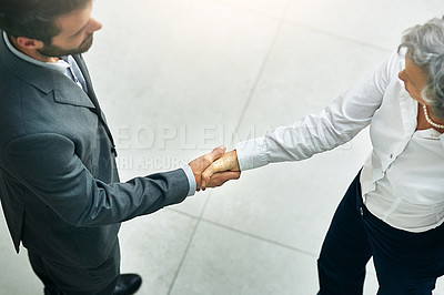 Buy stock photo High angle shot of businesspeople shaking hands in a modern office