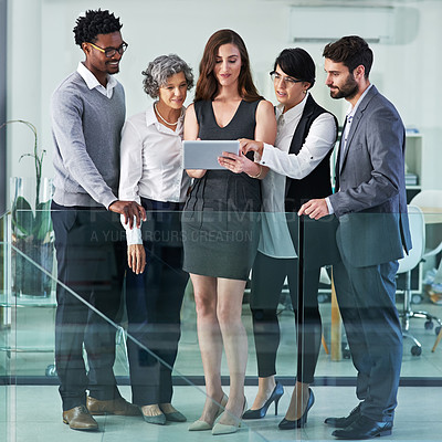 Buy stock photo Shot of a group of colleagues working together on a digital tablet in a modern office
