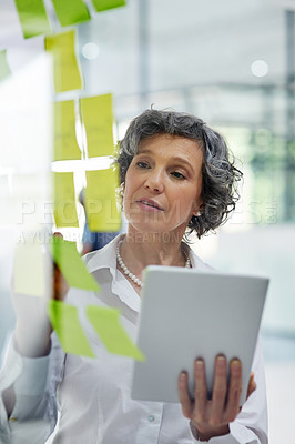 Buy stock photo Cropped shot of a mature businesswoman writing notes on a glass wall in a modern office