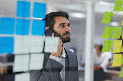 Buy stock photo Cropped shot of a young businessman talking on a phone while looking at notes on a glass wall