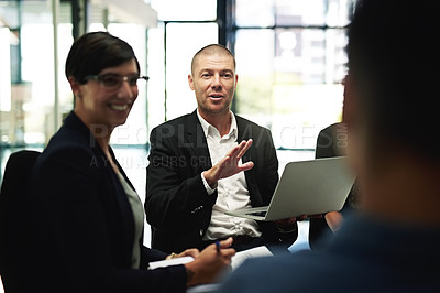 Buy stock photo Shot of a group of businesspeople sitting in a circle while having a meeting