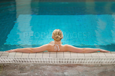 Buy stock photo Rearview shot of a woman relaxing in the pool at a spa