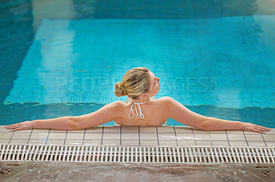 Buy stock photo Rearview shot of a young woman relaxing in the pool at a spa